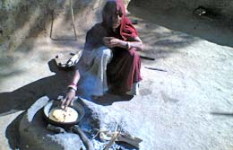 Tribal Rural housewife preparing food in open and traditional Chulla